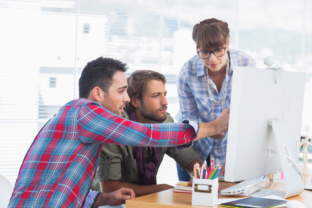 Team of designers working together on a computer
