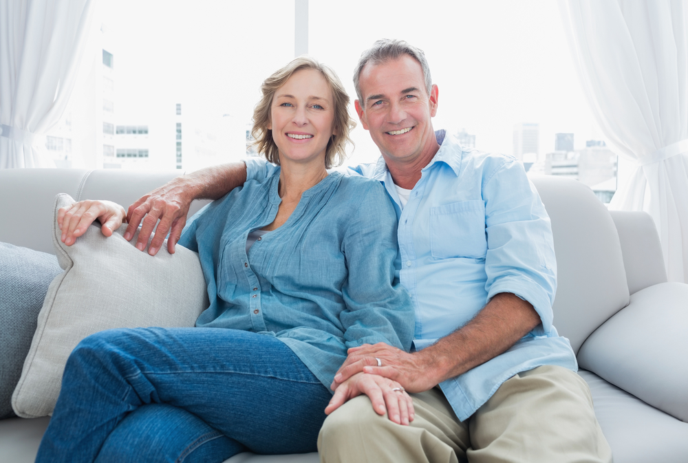 Middle aged couple relaxing on the couch smiling at camera at home in the living room